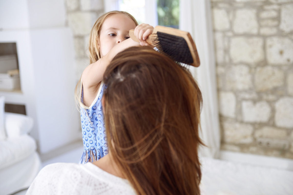 young girl combing mom's hair