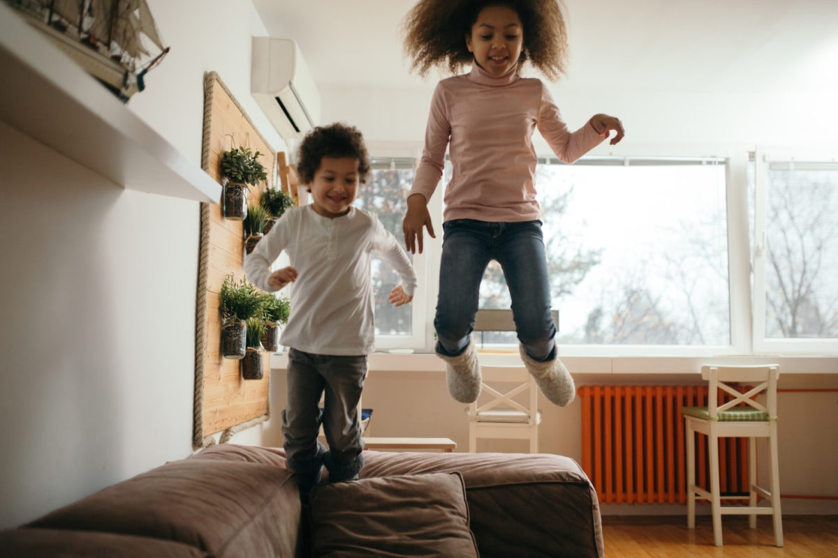 Children jumping on a sofa