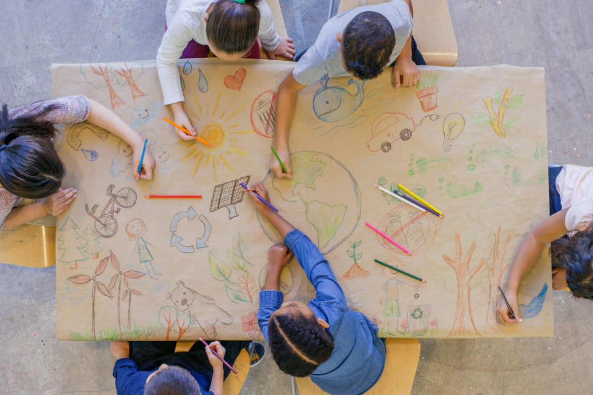 Children drawing on a table with color pencils