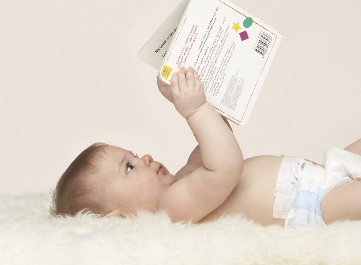 Baby reading a book while lying down on a bed
