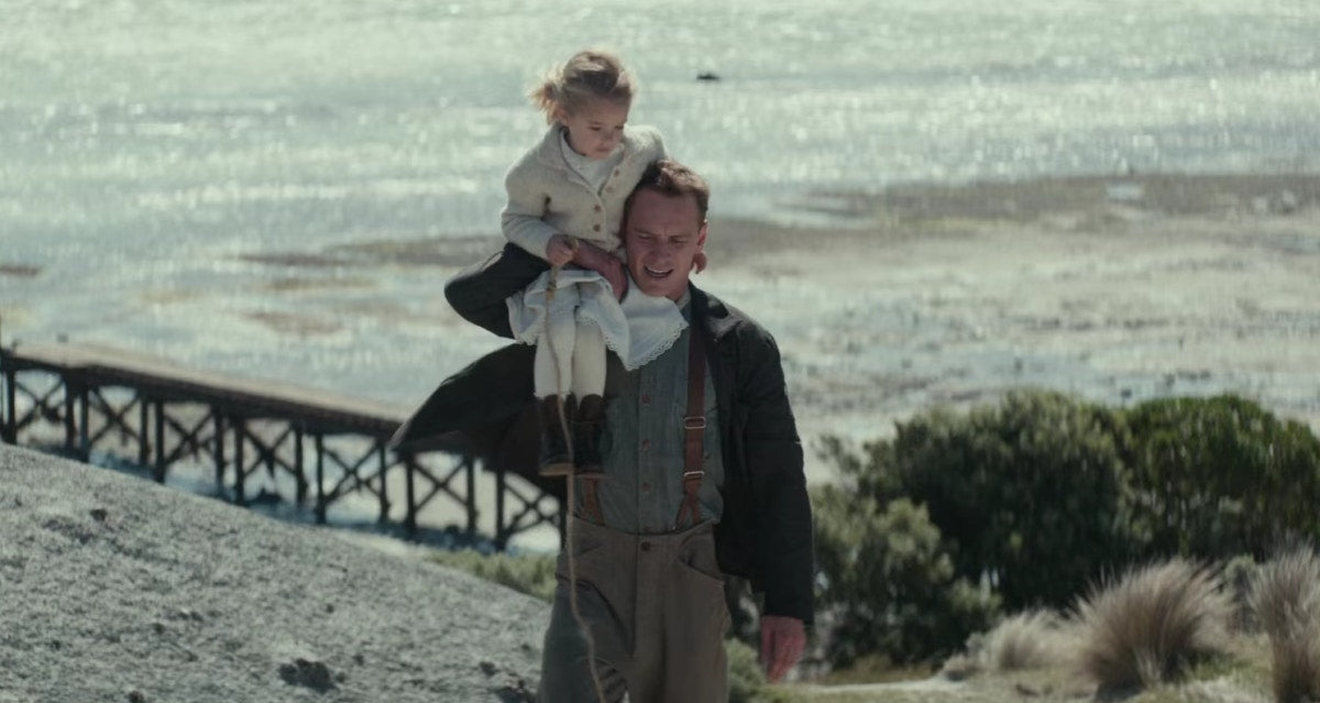 Little girl sitting on father`s shoulders