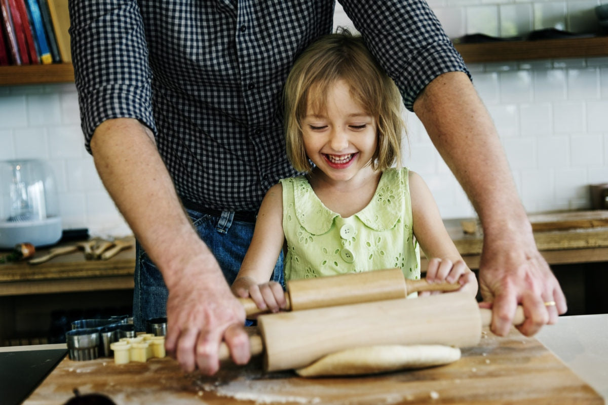little girl making dough for homemade cookies with her father