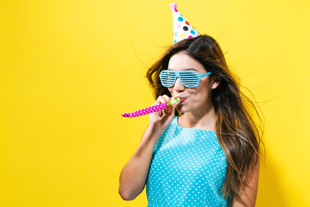 woman with party hat with noisemaker on a yellow background