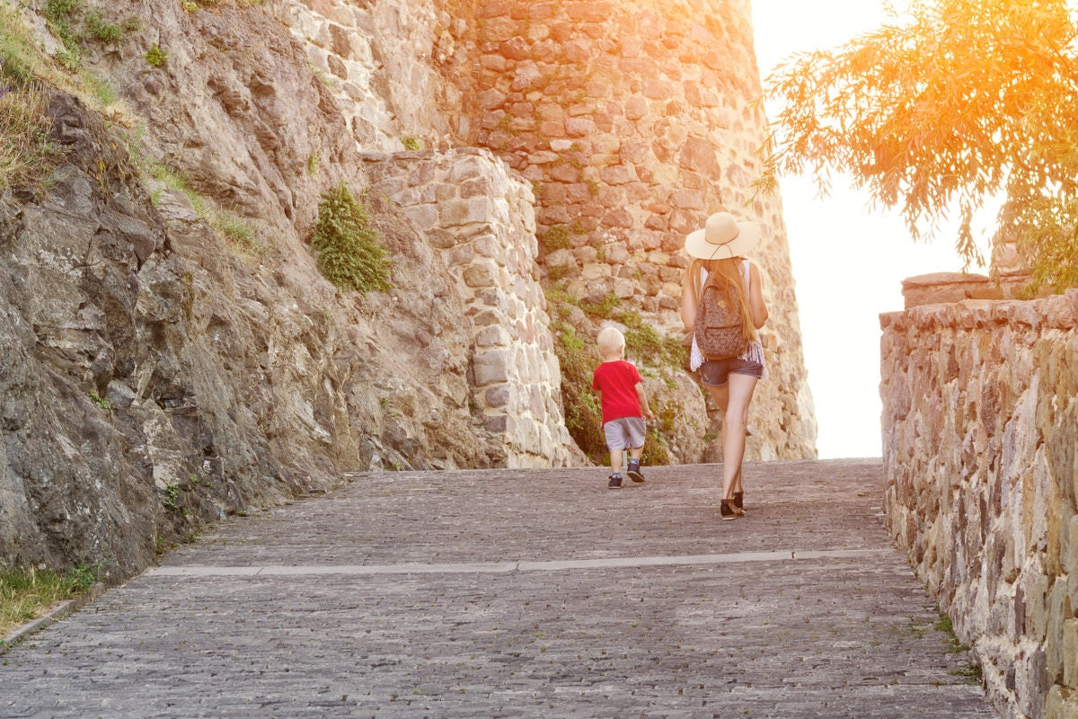 girl in a hat with a young son walking near the walls of the fortress