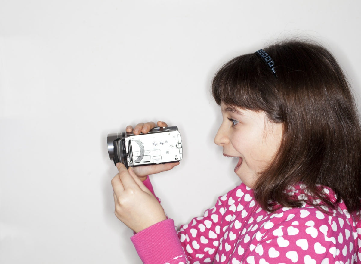 girl recording video at home with digital camera
