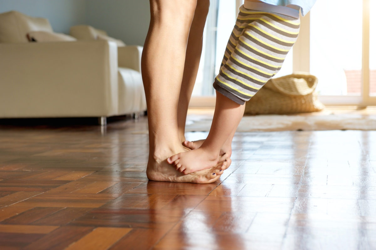 kid standing on mothers's feet