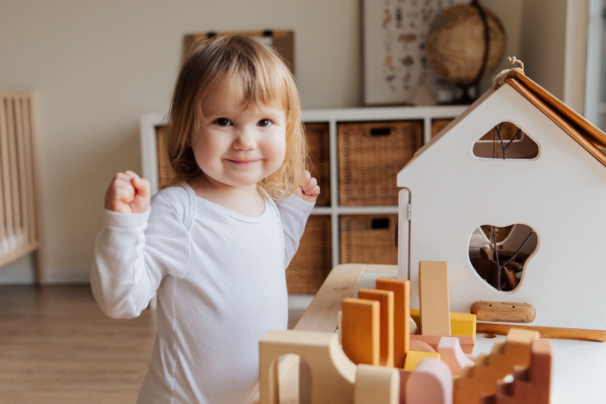 young girl next to a doll house
