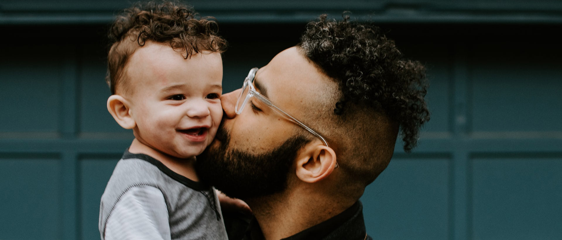 man carrying baby boy and kissing on cheek photo