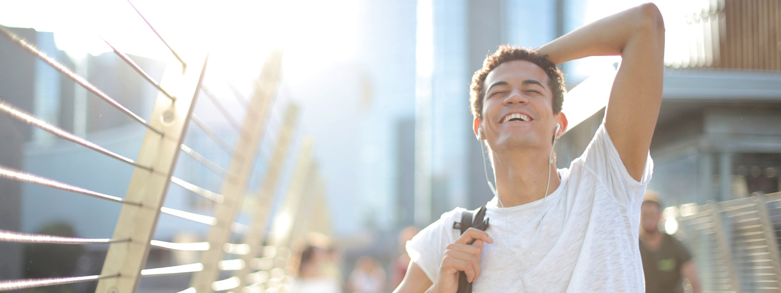 man walking across bridge looking up happy