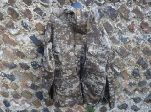 Camo jacket against a brick wall to prove it's durability and ability to blend in
