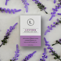 Lamarre Soap Co 5.3oz box of Lavender Natural Bar Soap with exfoliating lavender flowers, lavender essential oil, shea butter and coconut oil on marble counter with lavender flowers scattered about the counter.