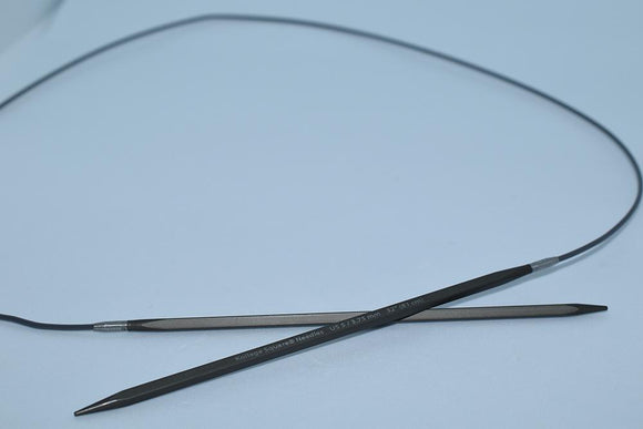 pair of grey metal square knitting needles