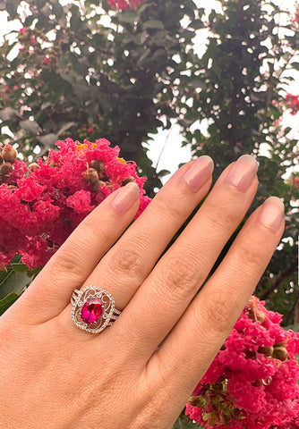 filigree white gold rubellite ring on hand with flowers in background