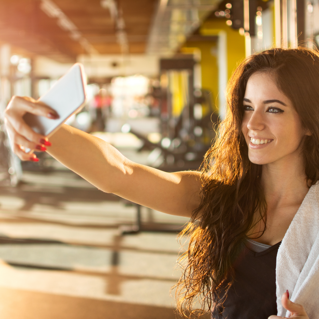 A woman clicking a photograph in a gym