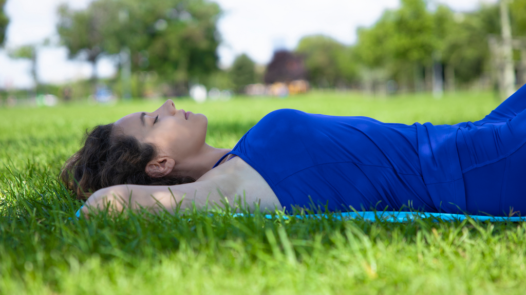 A Person Practicing Deep Breathing while Lying on The Grass