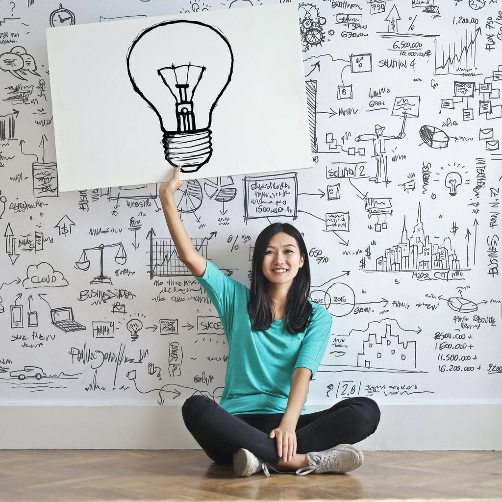 Person Holding a Light Bulb Drawing Above Their Head as a Metaphor for an Idea