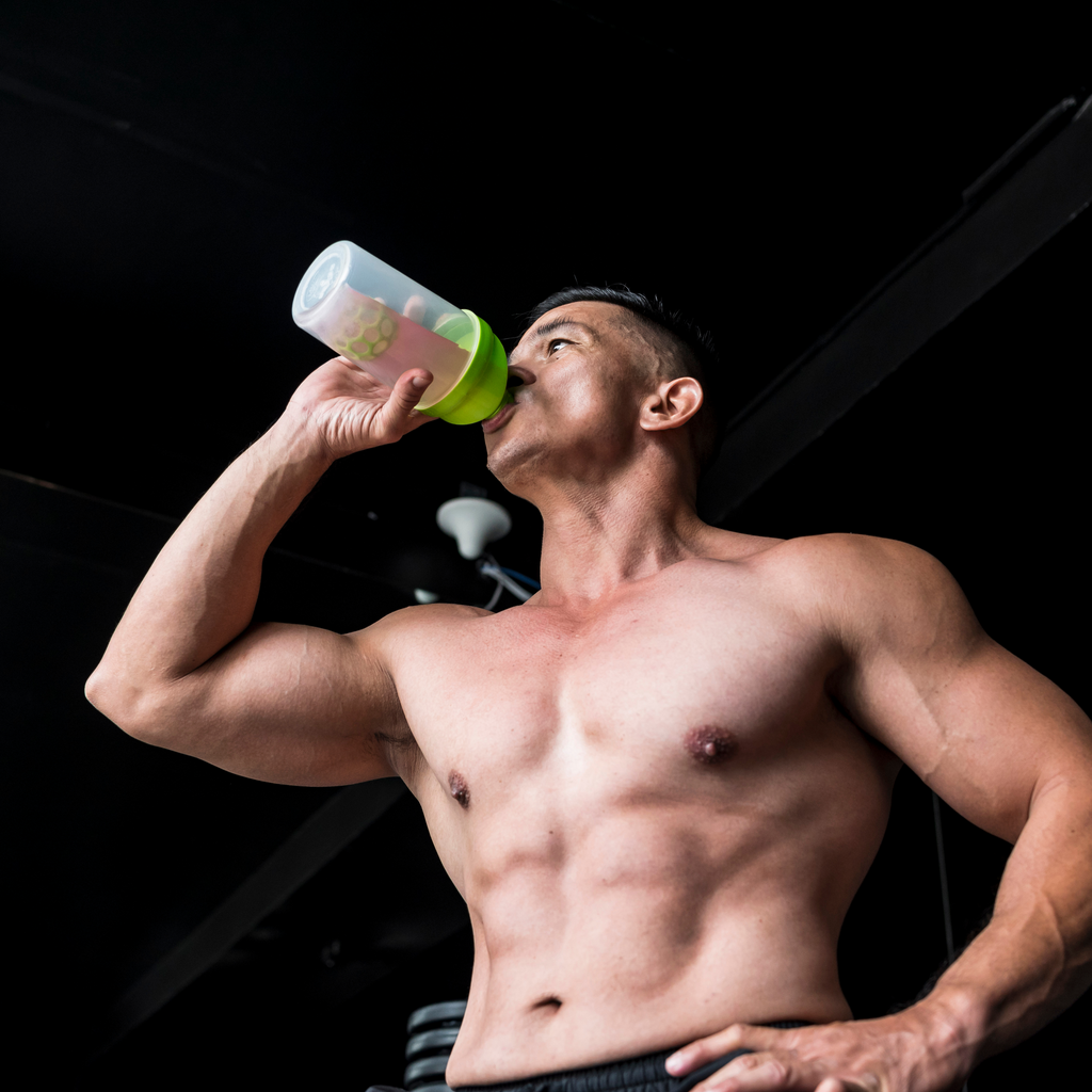 A fit man drinking pre workout drink