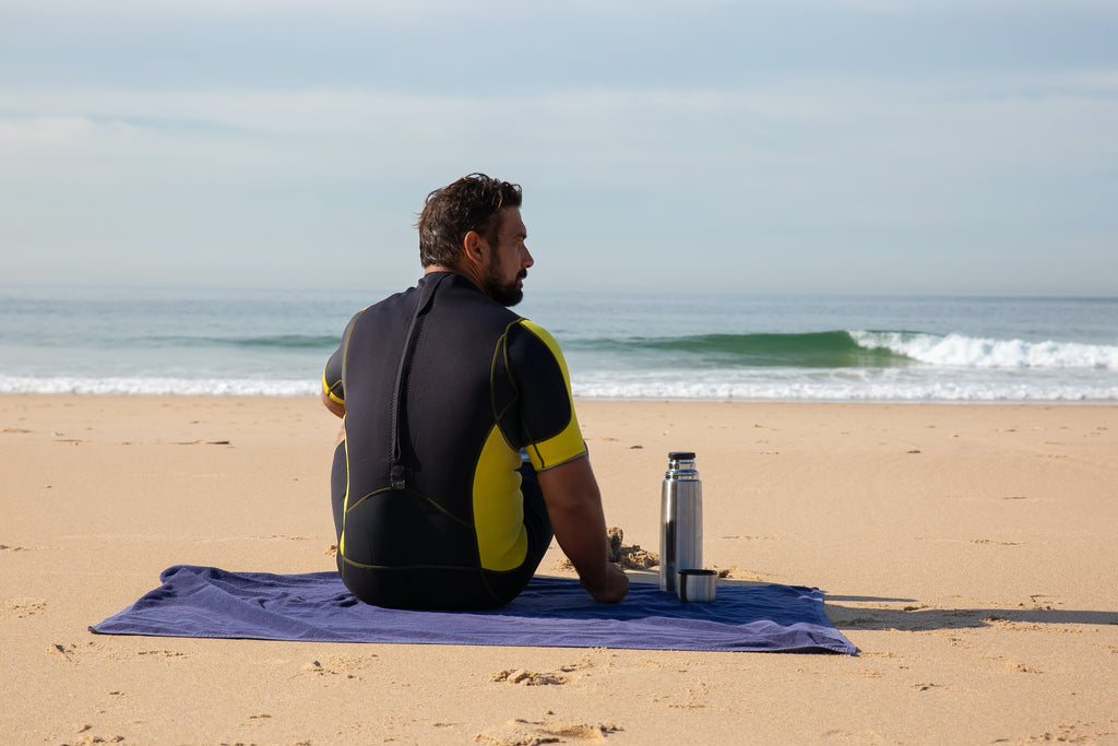 A Person Drinking Protein Shake on the Beach