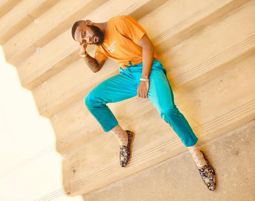 photo of male model on stairs outside wearing an orange tee shirt with bright blue slacks and the russel loafers in eden