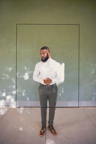 male model standing outside on concrete against a green wall wearing a white dress shirt with gray slacks and the jack boot in eden