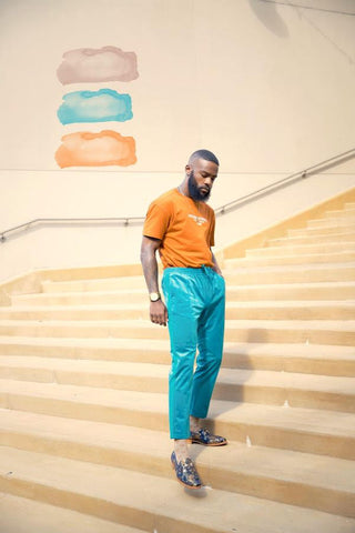 male model outside on stairs wearing an orange tee shirt with bright blue pants and the russel loafers in eden
