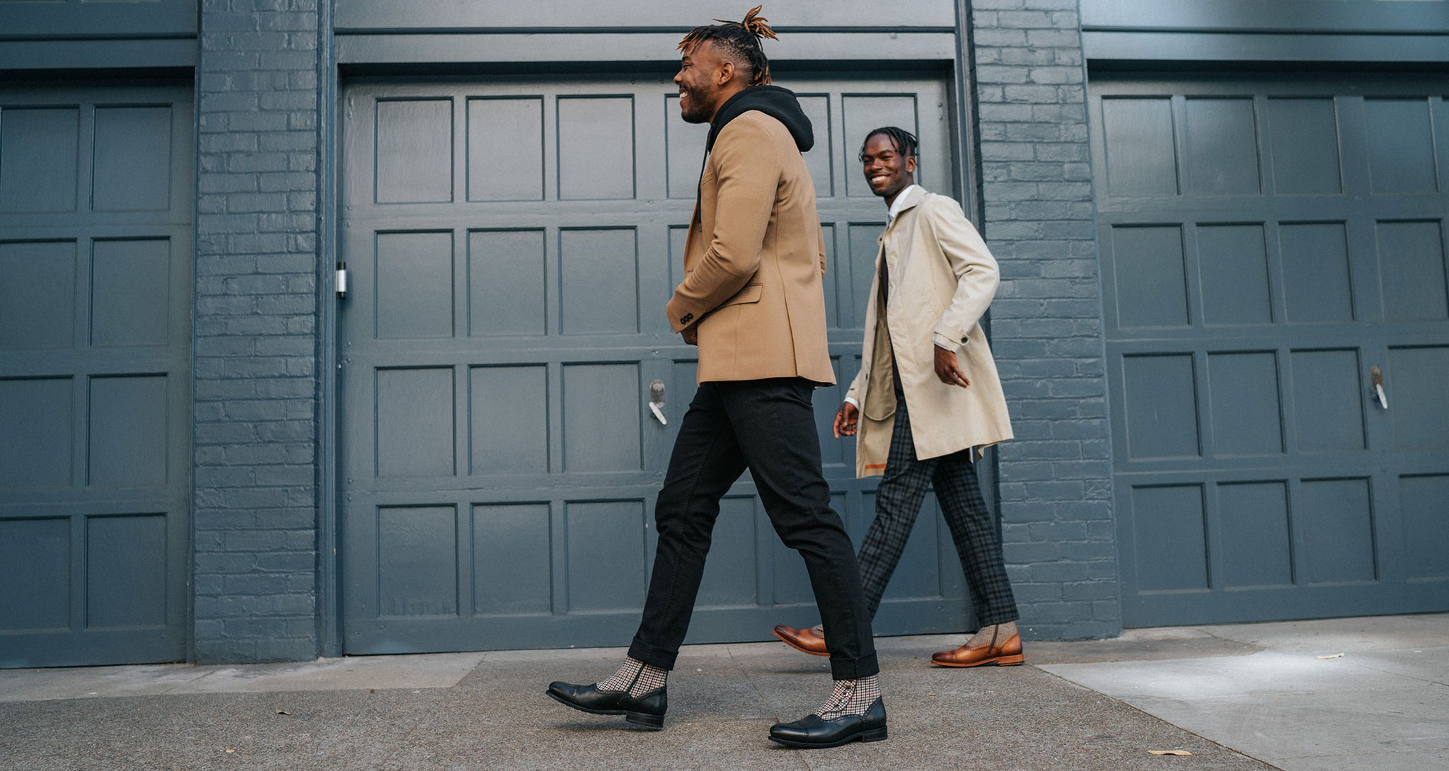 two models walking in the holt boot black and holt boot honey