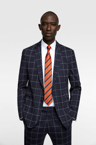 male model in blue plaid suit with orange tie