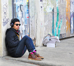 hipster boy sitting against graffitied wall