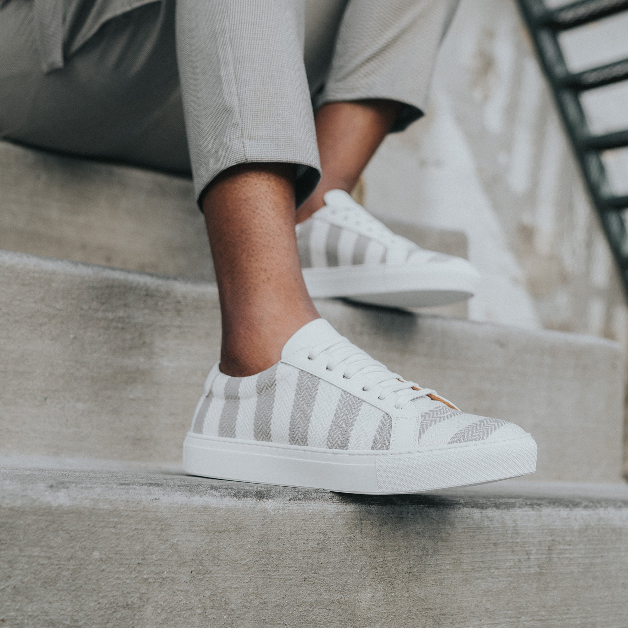model sitting on stairs wearing the sneaker in grey stripes