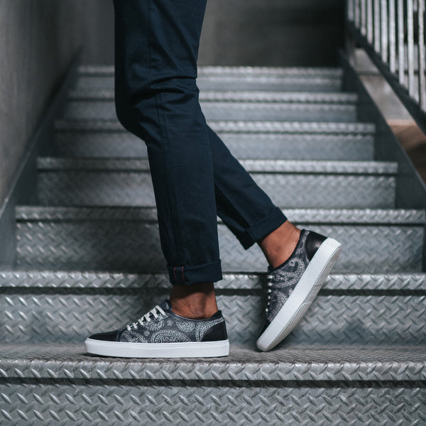 model on stairs wearing the jack sneaker in blue paisley