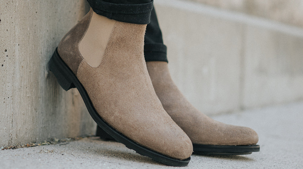 The Drake Boot in Gaucho on model standing on a concrete wall with one heel kicked up against the wall