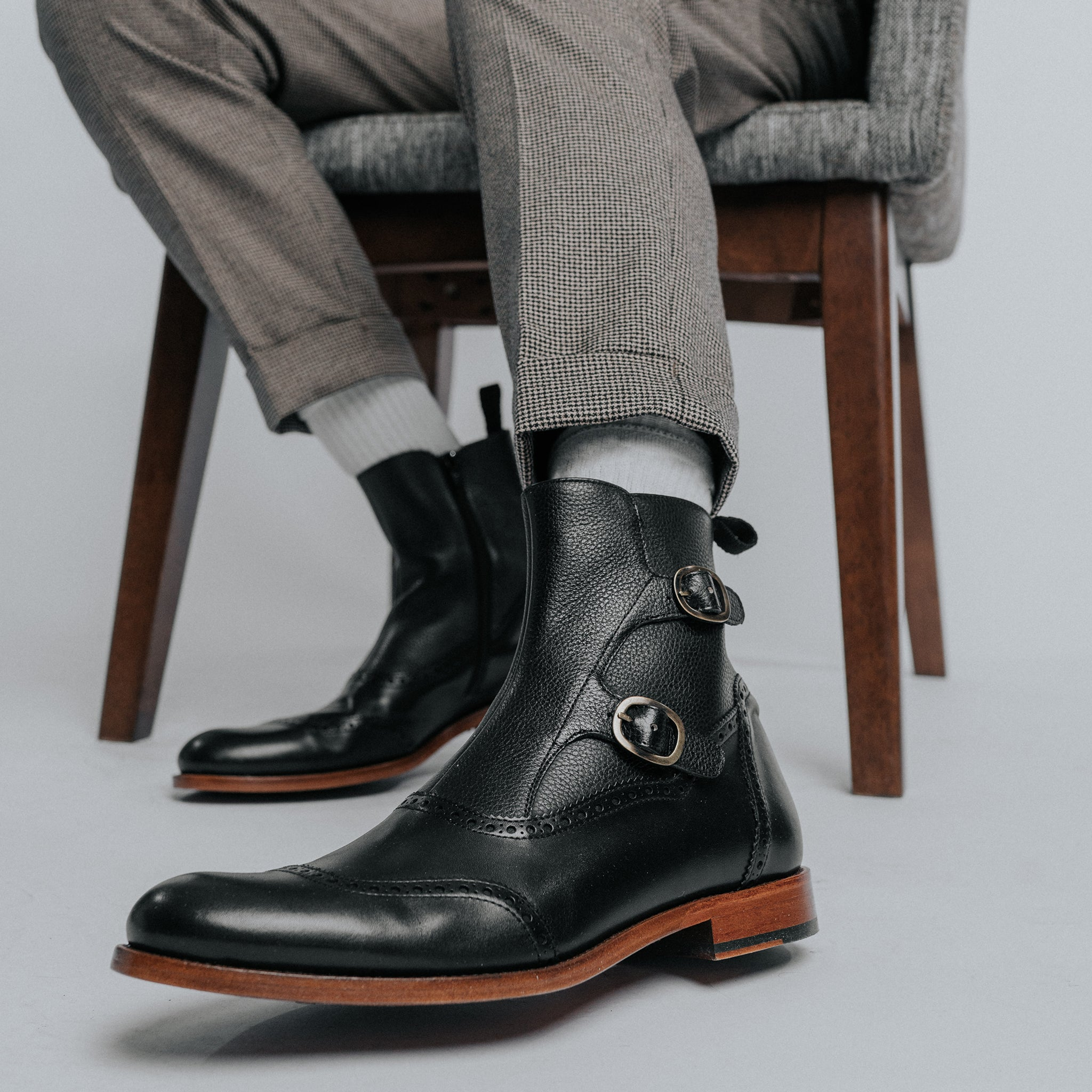 The Dustin Boot in Black on model sitting in a wooden chair wearing white socks and checkered pants