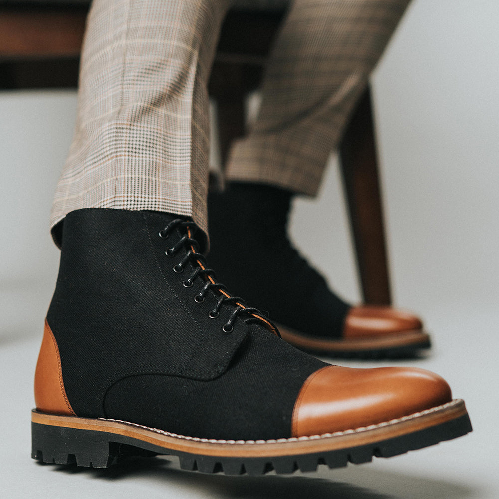 The Jack Boot in Industrial on model sitting in a wooden chair wearing plaid pants