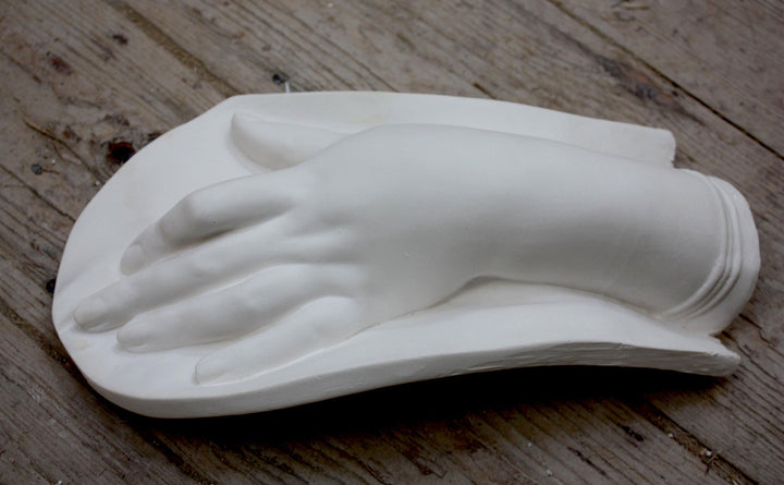 photo of plaster cast of female hand on low curved panel on wood floor