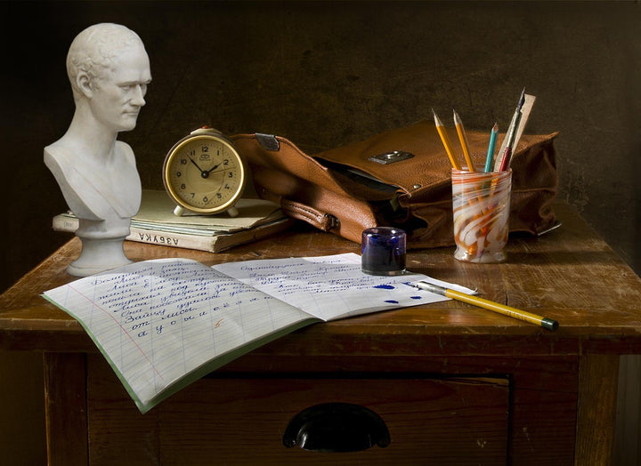 photo of dark wooden desk with open notebook and pen and ink, jar of pencils, small clock, leather bag, books, and plaster cast bust of Alexander Hamilton