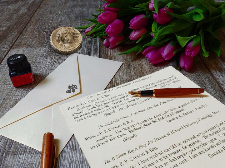 photo closeup of gray textured desktop with written letter, envelope, wooden-colored pen and pen cap, small square jar of ink, off-white small round plaster relief of Infant Bacchus, and top of bouquet of purple tulips lying on its side