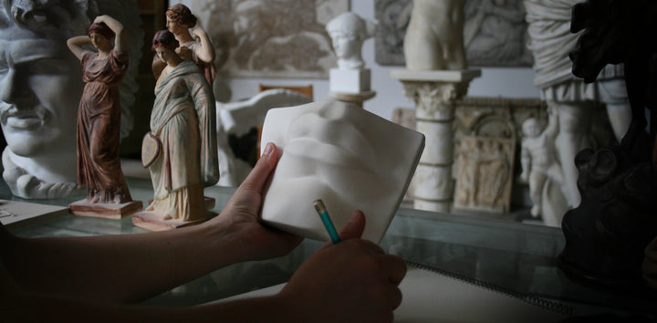Photo of someone's hands holding a pencil and holding Michelangelo's David mouth cast in the gallery