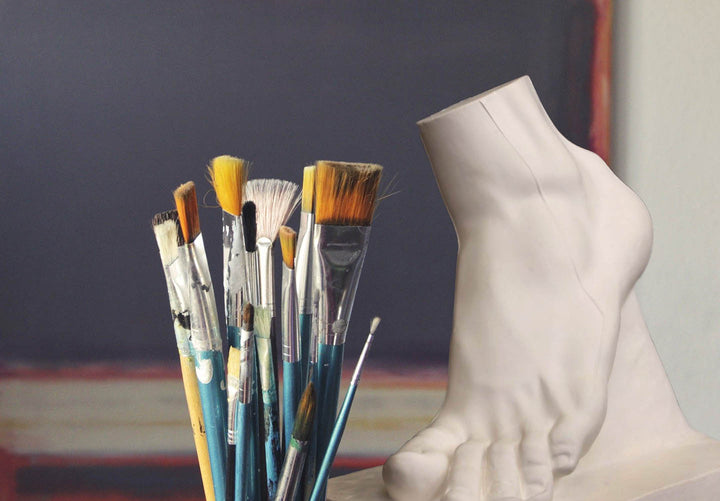 Photo of paintbrushes and plaster cast of foot in art studio
