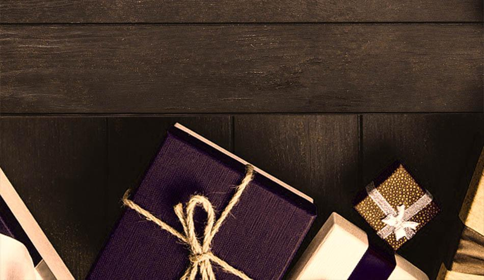 photo of gold, white, and purple presents on a wood table
