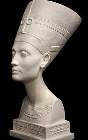 photo of plaster cast sculpture of bust of Nefertiti with crown and decorative collar on a decorative base with a black background
