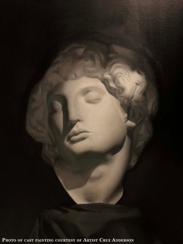 Photo of cast painting of sculpture bust on a black background