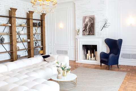 photo of large white L-shaped sectional in the foreground and middle-ground with a white and gold coffee table in a white-walled room with ornamental plaster-work and white brick, wood floor, and gray area rug, and blue chair beside a white fireplace and large modern wooden bookshelf