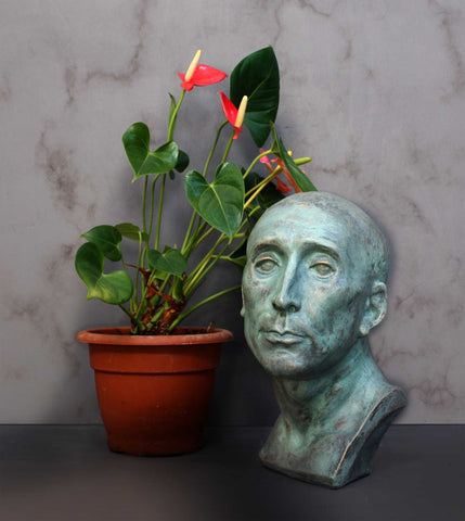 photo of plaster cast sculpture bust of man, namely Niccolo da Uzzano, in verdigris patina next to plant with pink flowers in brown pot in front of a white marble wall and on a gray surface