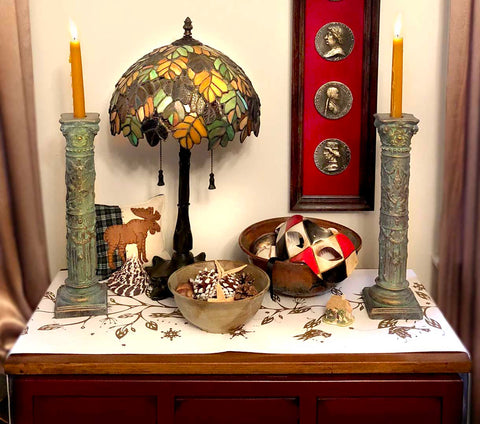 photo of small table with patterned, white tablecloth, two verdigris-color plaster candlesticks with lit orange candles, colorful glass lamp, decorative bowls with pine cones and a Venetian mask, pillow with moose image, and on off-white wall behind, a tall, narrow shadow box with three silver portrait medallions on red background