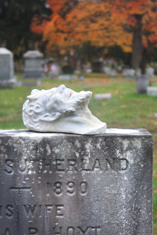 photo of plaster cast sculpture of a satyr head atop a gray headstone in the foreground in a cemetery