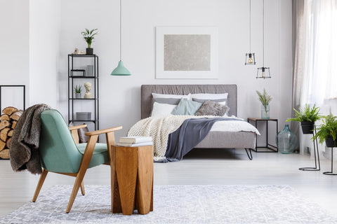 photo of bedroom with gray bed and headboard with white, blue, and mint-green blankets and pillows in background and mint-green and wooden modern chair and wooden side table in foreground and various plants, lamps, and other items