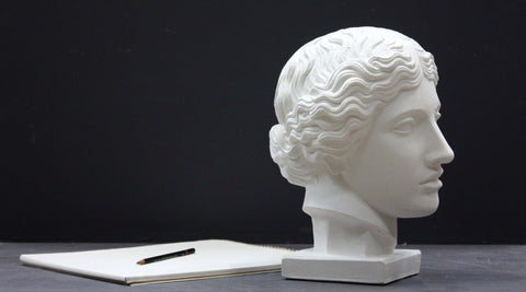 Photo of plaster cast of an Amazon Head with a sketchpad and pencil to the left on a black background