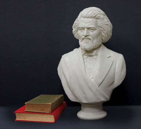 Photo of white plaster cast sculpture bust of Frederick Douglass with beard and in suit coat with toga over one shoulder and a green book stacked atop a red book beside it on dark gray background