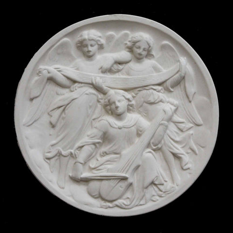 photo of plaster cast relief of three angels, two holding a long scroll and one playing a string instrument on a black background