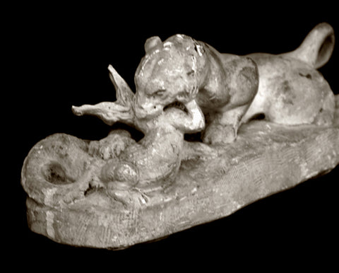 Photo of original plaster Caproni cast of a tiger devouring a crocodile on a black background